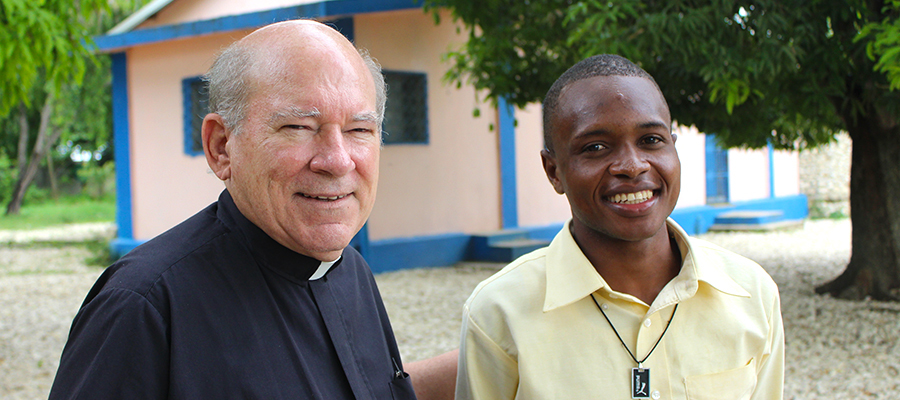 Father Glenn Meaux and a scholarship recipient at the Kobonal Haiti Mission