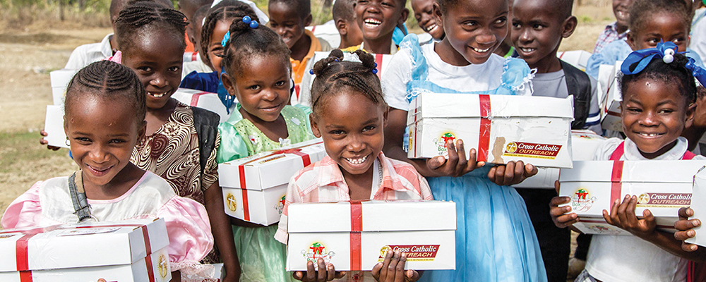 Group of children holding their Boxes of Joy and smiling