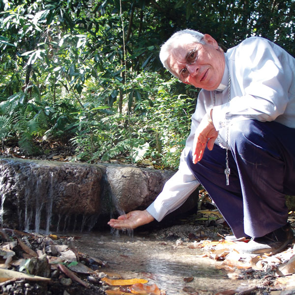 Bishop Grullon photo, dipping hand in creek