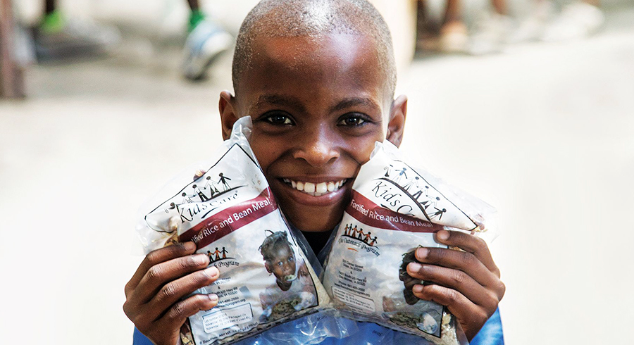 A child in Haiti holds up bags of nutritious Vitafood