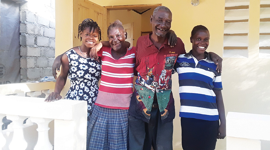 A Haitian family stands in front of their new home