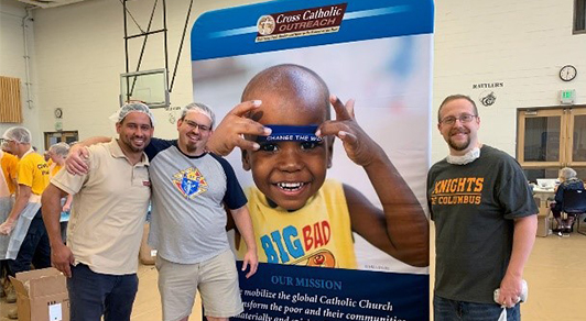 Cross Catholic Outreach and Knights of Columbus at a food packing event