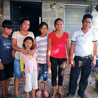 A Guatemalan family of six stands in front of a concrete-block house constructed with help from Cross Catholic Outreach.