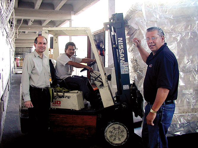 In 2003, President Jim Cavnar (left) works with Vic Gonsalves (right), Cross Catholic Outreach's first director of Gifts in Kind, to prepare a shipment of relief materials.