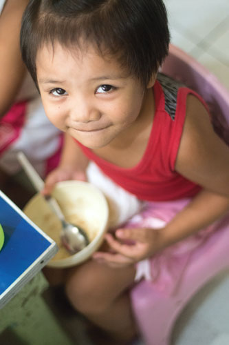 A little girl in the Philippines finishes a hearty meal.