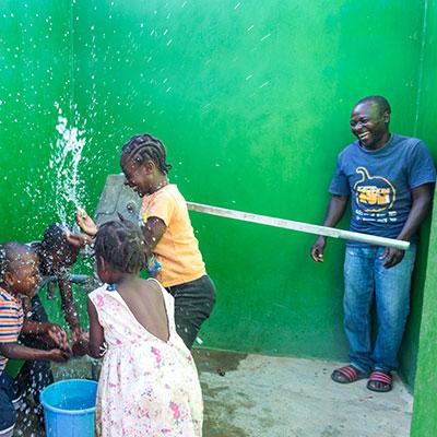 A Haitian family at a clean water pump.