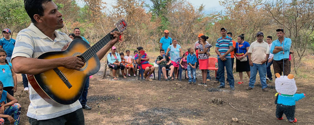 Nicaraguan man plays guitar at blessing of land where homes for 21 poor families were built.
