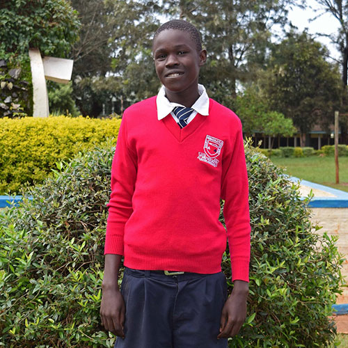 Duncan Ejikon proudly wears his school uniform on the manicured grounds of his Catholic boarding school.