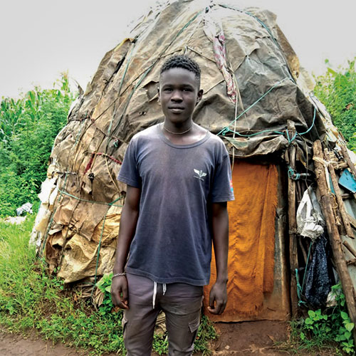 Duncan Ejikon stands in front of his family's makeshift home made from sticks and fabric scraps.