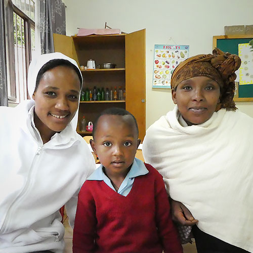 A Catholic sister sits with 5-year-old Gelana Reta and his mother inside a classroom at Shambu Catholic Kindergarten in Ethiopia.