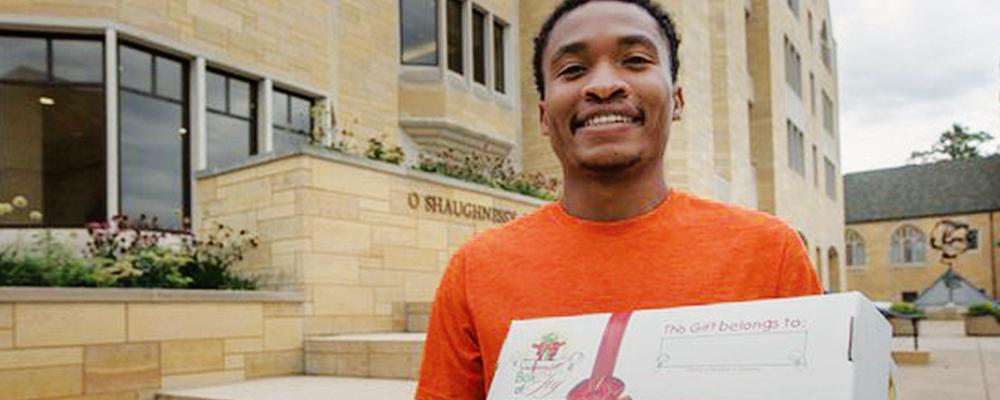 Josh Mounsey, a student at the University of St. Thomas, holds a Box of Joy.