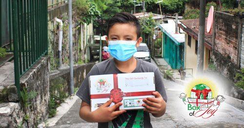 Boy wearing mask in El Salvador holds Box of Joy on street near home.