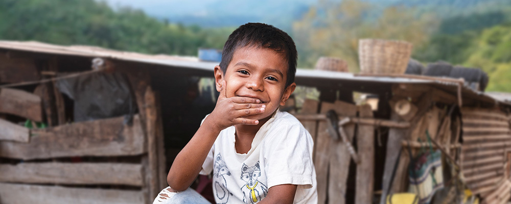 Hopeful Guatemalan boy covers a smile with his hand