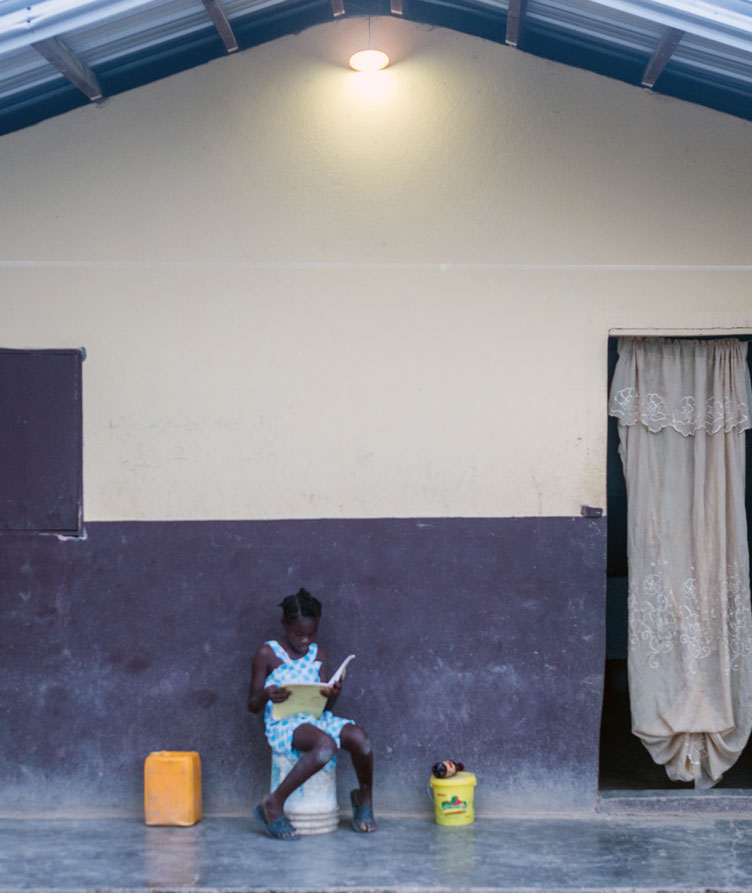 Student doing her homework under a light.
