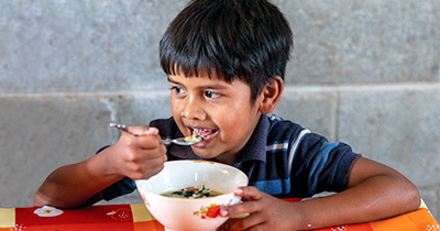A boy holds a bowl of nutritious food.
