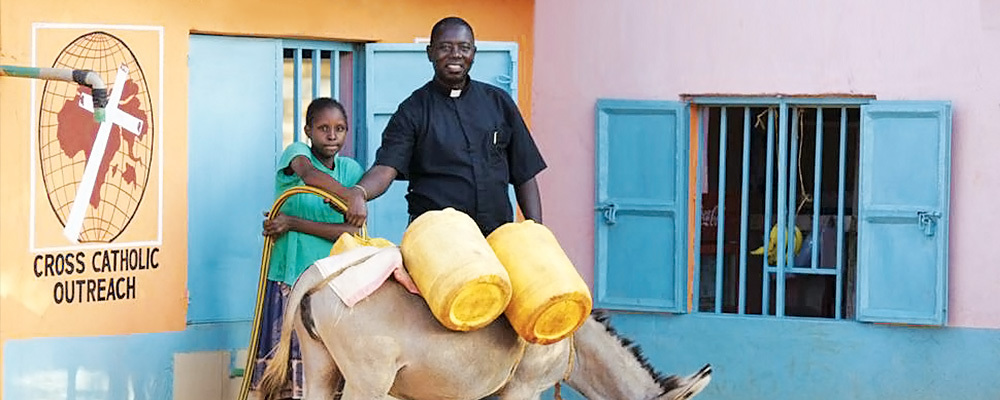 Fr. Fabian helps a girl in Tawa, Kenya, collect water from the new water kiosk.
