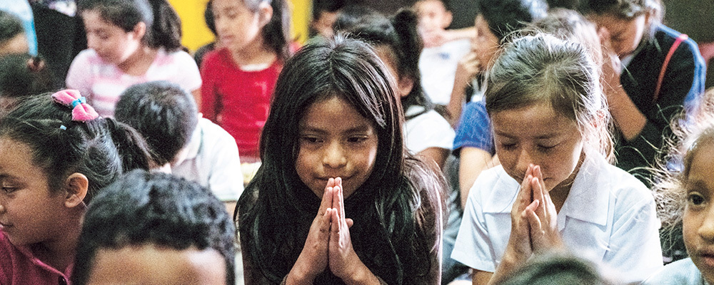 A gathering of Guatemalan children with their hands pressed together in prayer.