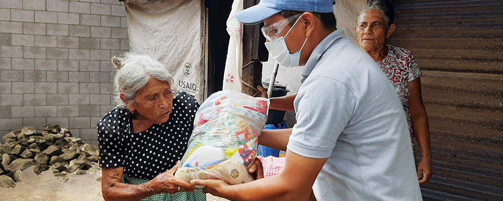 A man in a face mask hands a bag of food supplies to an elderly woman in need.