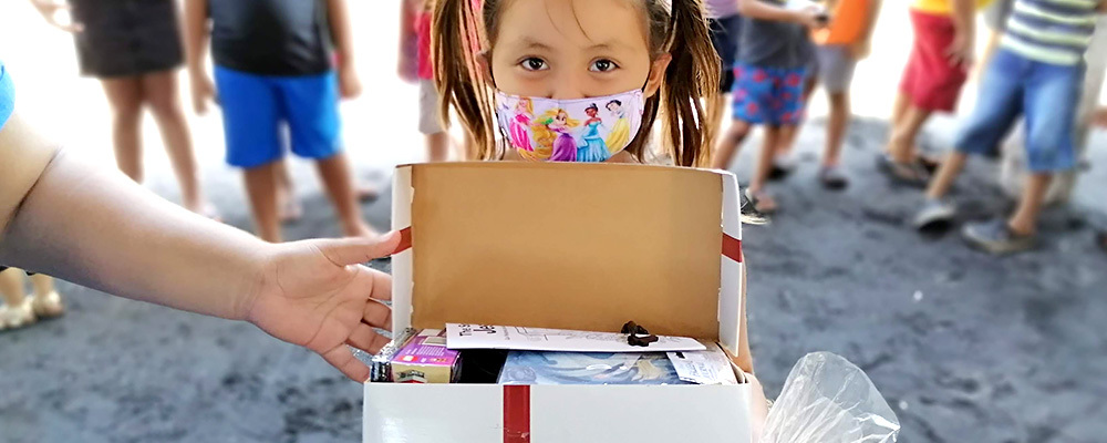 A little girl wearing a face mask holds her opened Box of Joy.