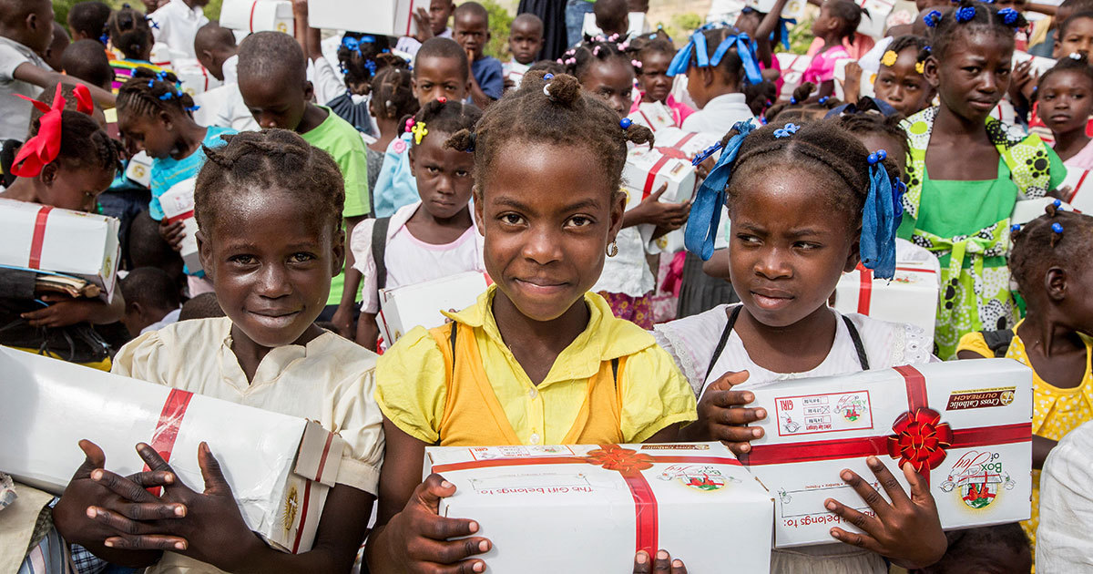 Smiling Haitian children hold up Christmas gift boxes they received.