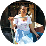 A woman stands outside a dilapidated home.