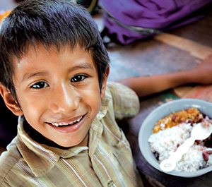 A boy in Nicaragua smiles while eating a meal.