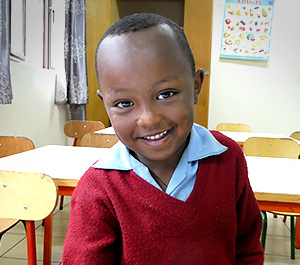 A young boy in Ethiopia smiles while wearing a school uniform.