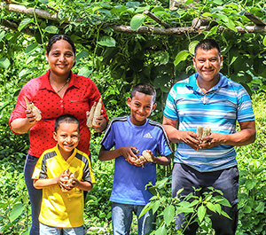 A family in Nicaragua stands in a field with their vegetables.