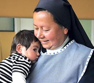 A Catholic sister in Ecuador holds a small boy.