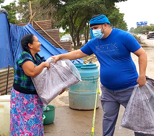A man in Honduras hands a bag of supplies to a grateful woman outside a tarp-covered structure.