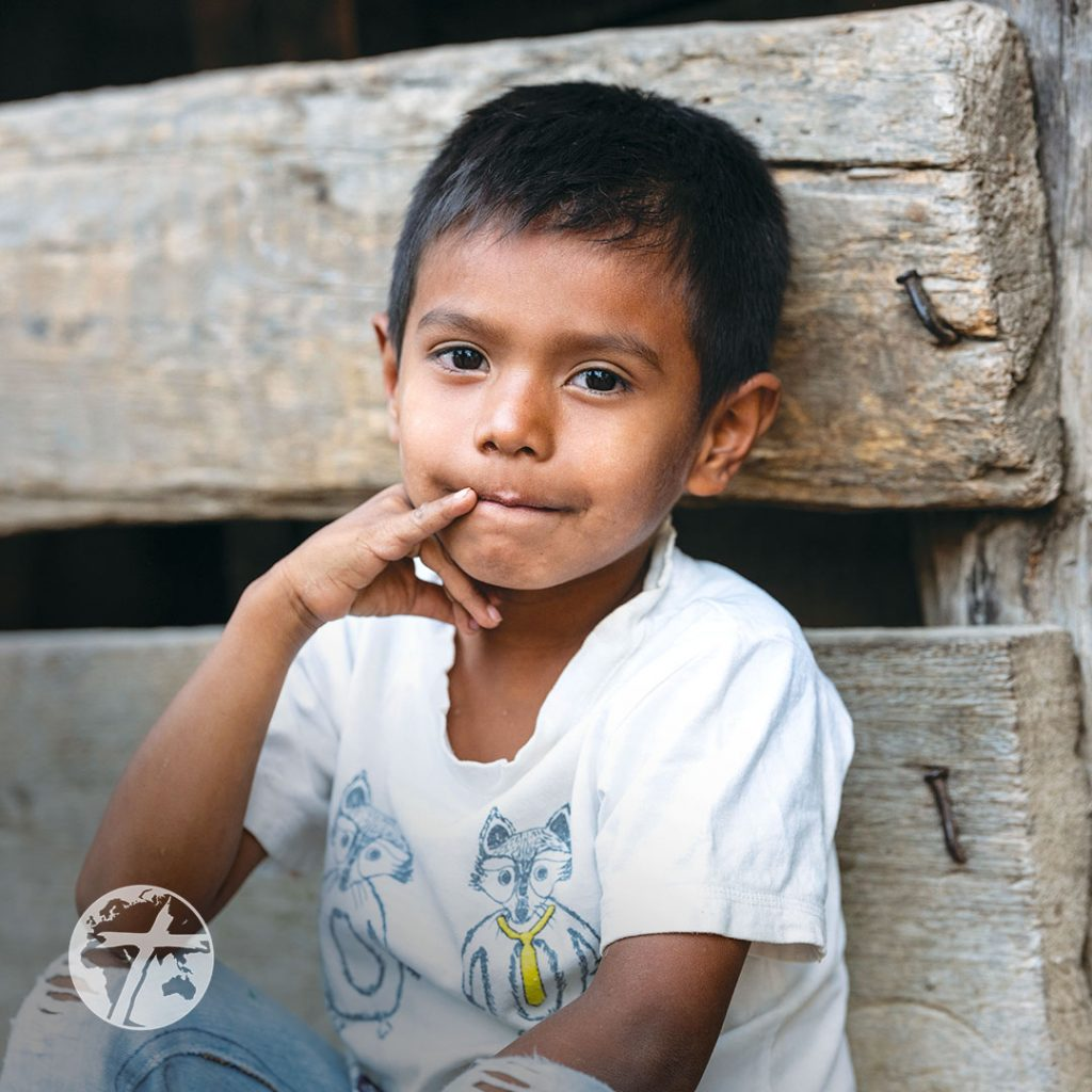 A Guatemalan boy sits outside a dilapidated home.