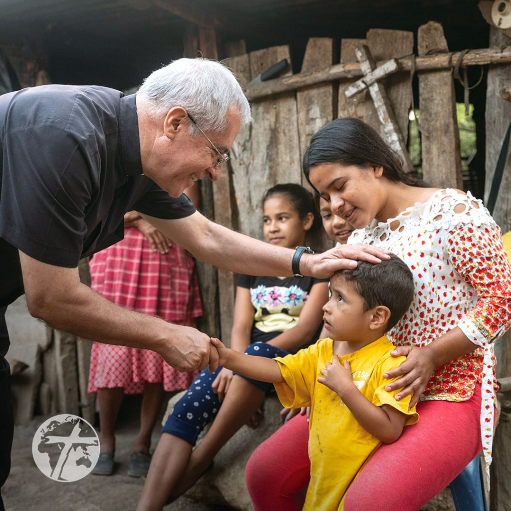 A priest comforts children outside a dilapidated home.