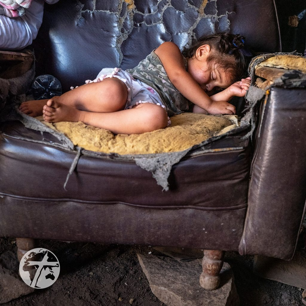 A small girl sleeps on a damaged couch inside a dirt-floor home.