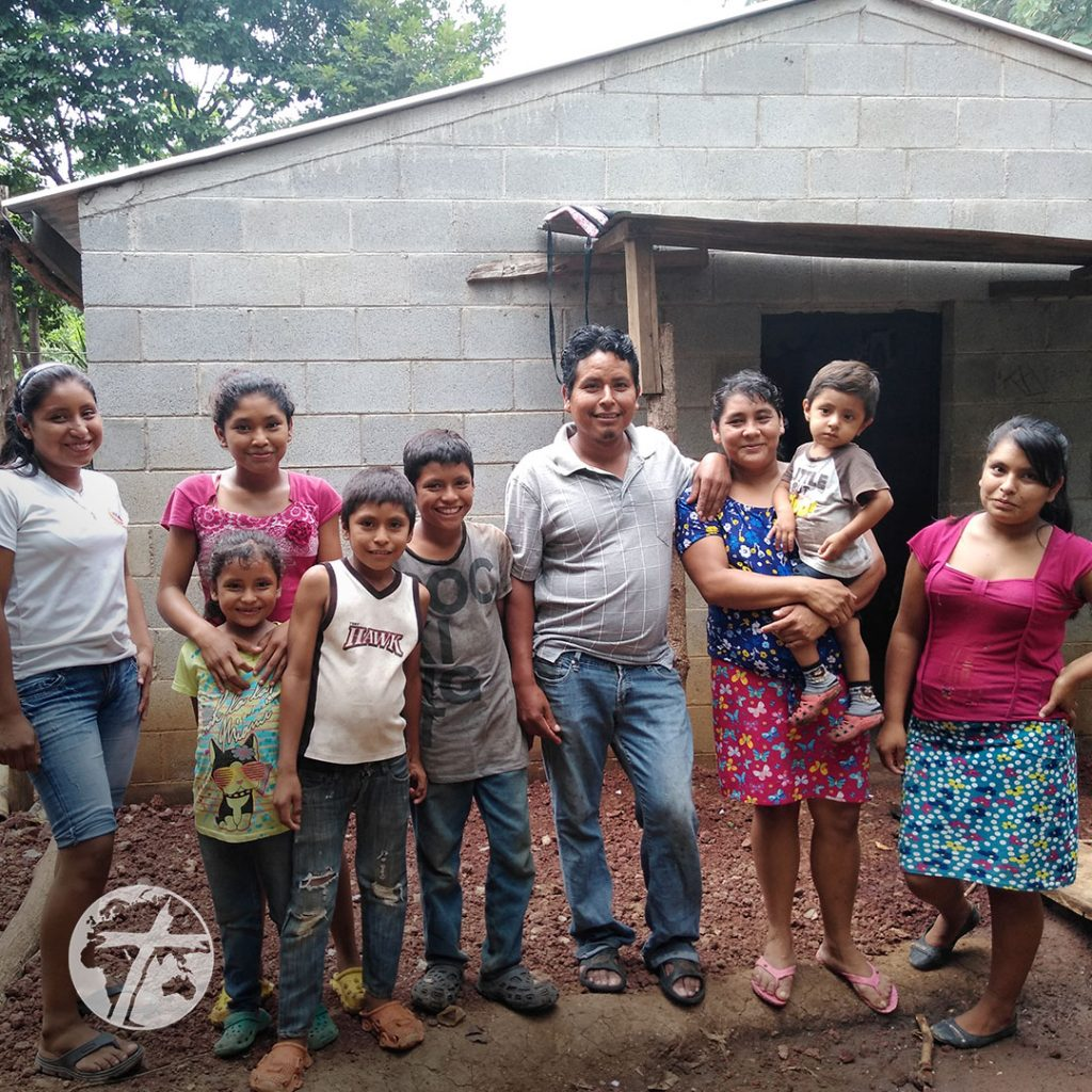 A family stands outside a concrete house.