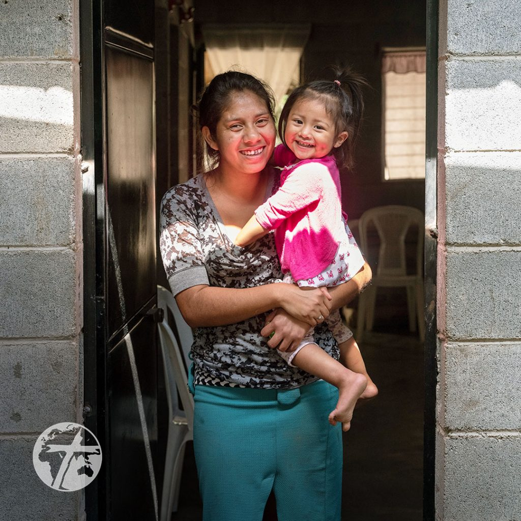 A mother and daughter smile in the entrance to a concrete home.