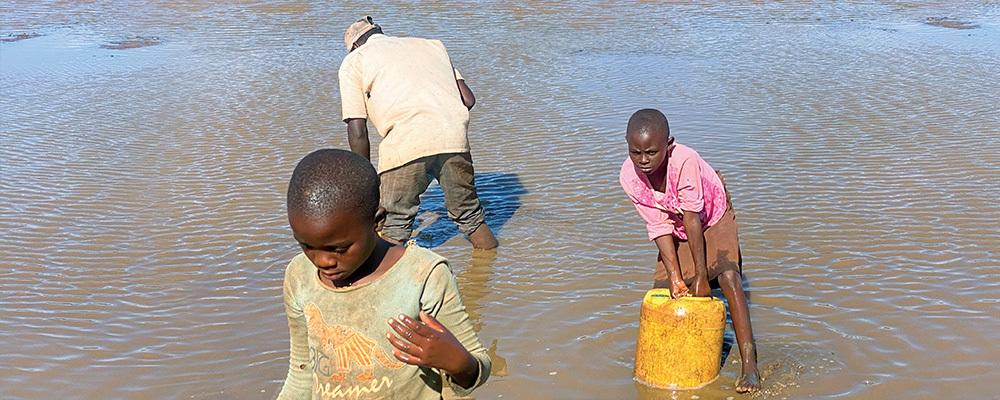 Felicia, Amina and another villager collect water at a lake near Kamtonga, Kenya