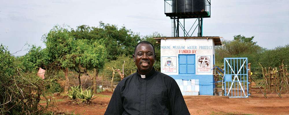 Father Fabian Hevi stands in front of a water kiosk in Mokine, Kenya