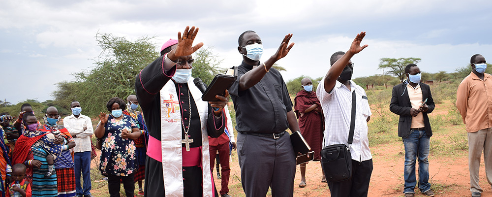 Archbishop Martin Kivuva Musonde and Father Fabian Hevi pray with community members to bless the new water system in Orkung'u, Kenya
