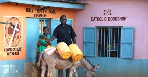 Father Fabian Hevi helps a little girl at the water kiosk in Tawa, Kenya