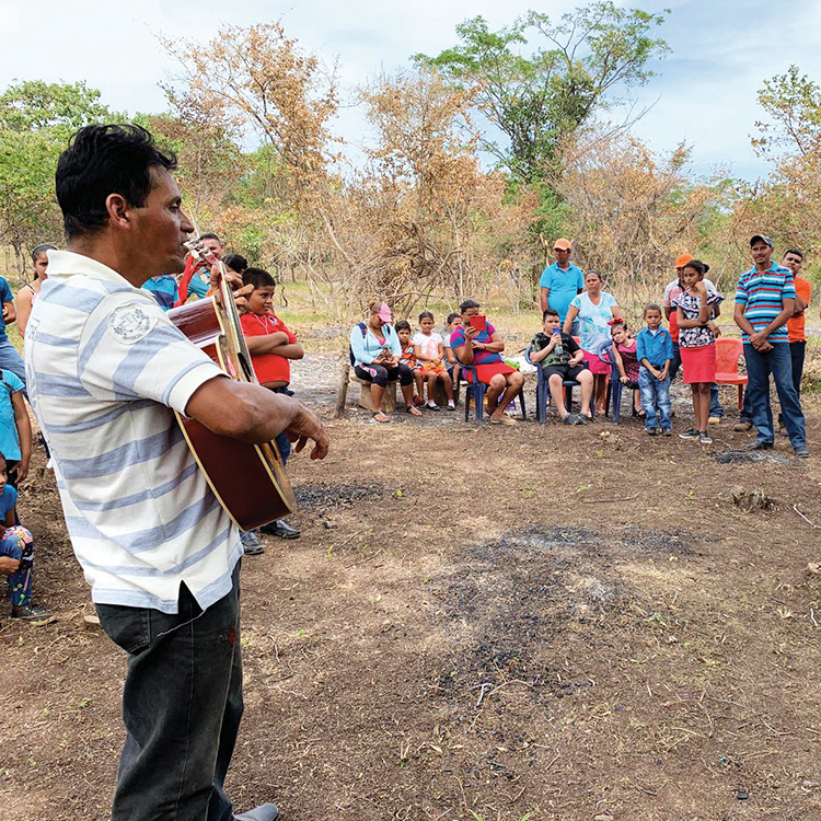 Community members gather around a guitarist and pinata during a blessing ceremony for a construction site.