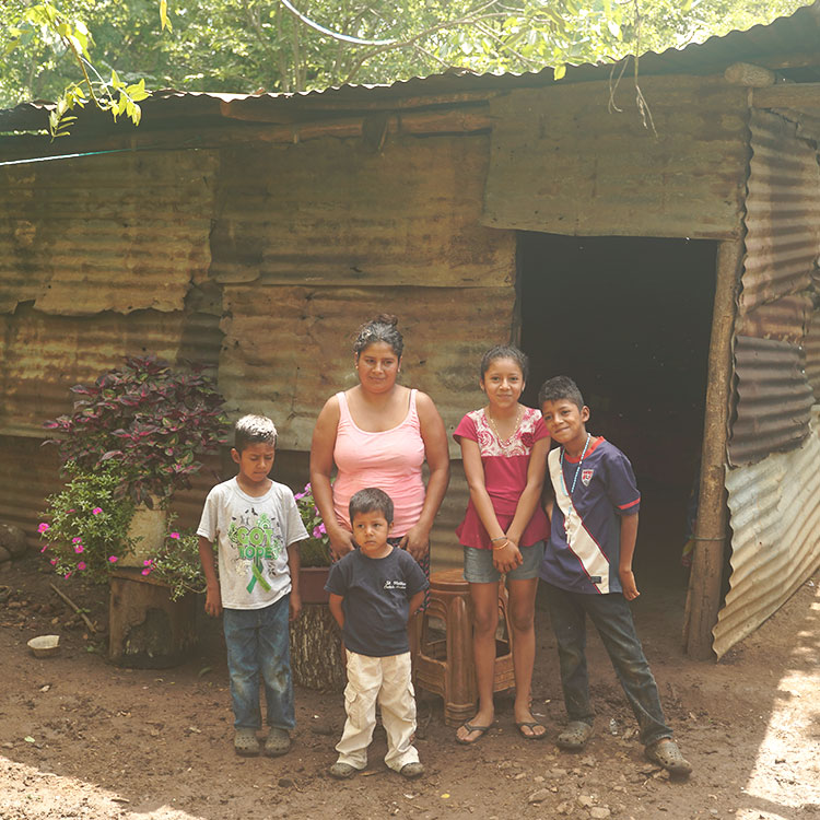 Reina Lima and her children outside their makeshift house. They are one of the 107 families you can bless with a new, safe home.