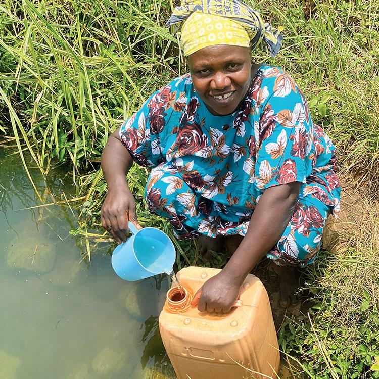 Agnes Mwakuja Matenge collects water from pond in Sagalla, Kenya