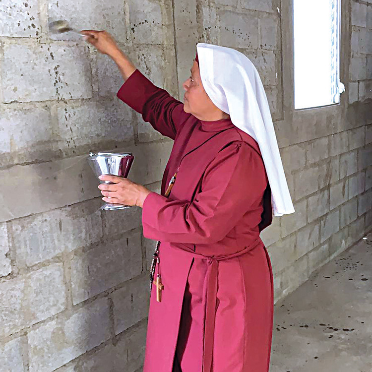 A Catholic sister sprinkles holy water on the inside wall of a new house while a woman and child look on.