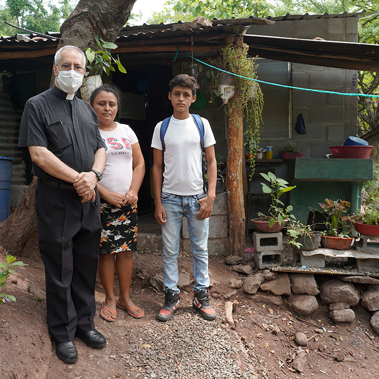Fr. Raúl with Rosa and Junior Pérez outside their home. Your gift will bless Junior and 81 other students with scholarships to attend a new Catholic school.