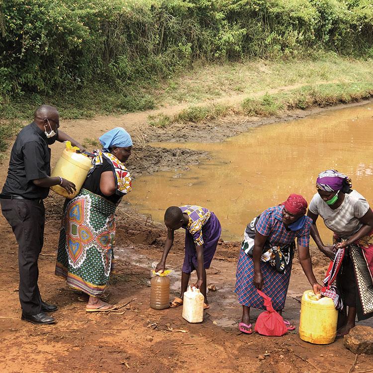 Father Boniface helps Ruth Mugau lift her water container at a muddy lake near Orkung'u, Kenya