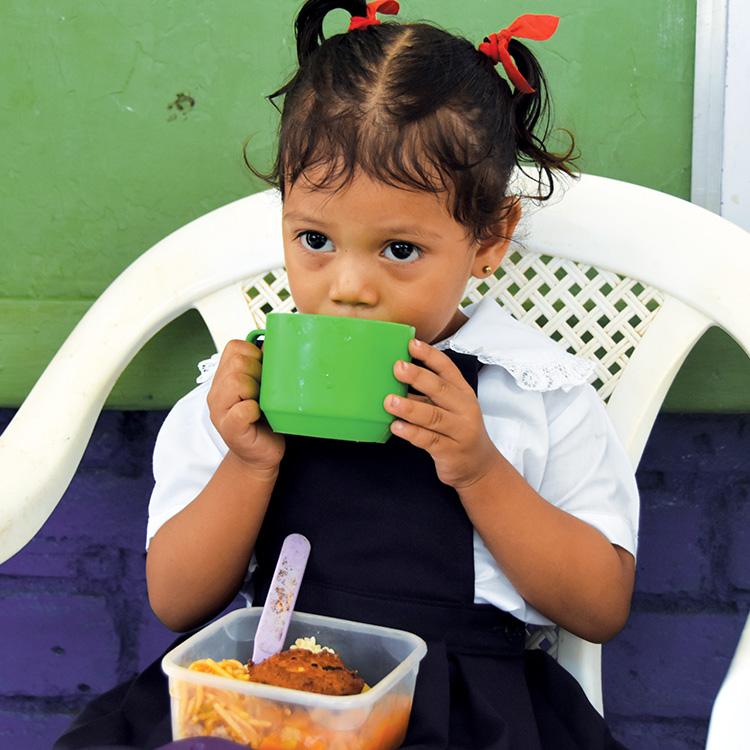 A Nicaraguan girl in a school uniform eats her lunch at a Rainbow Network feeding center.