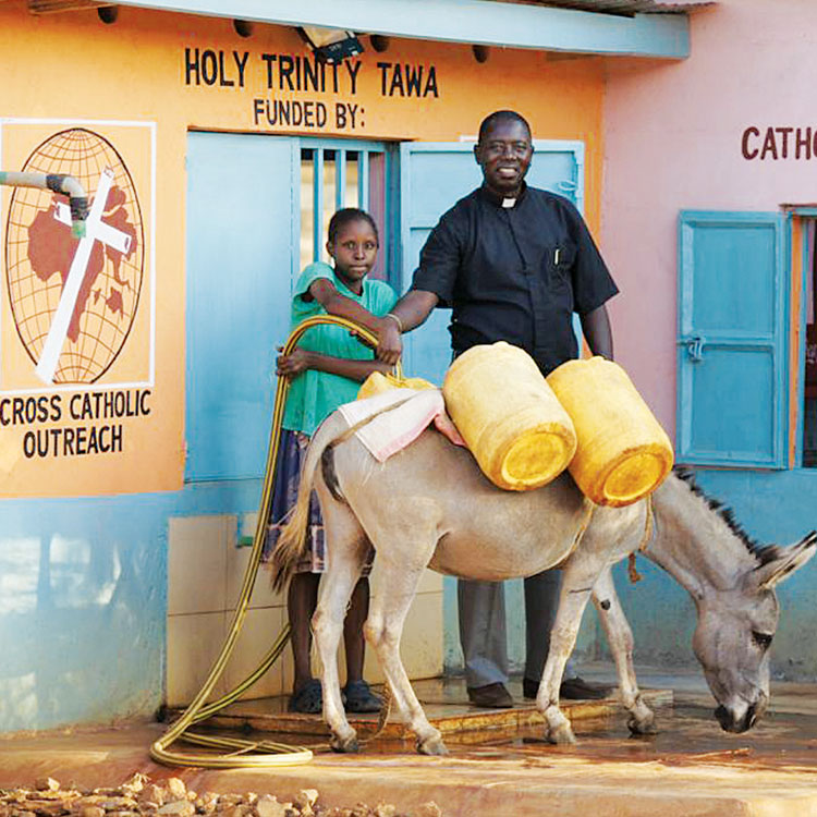 Father Fabian helps a girl fill her containers at the water kiosk in Tawa, Kenya