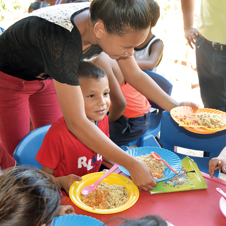 Women distribute meals to seated children at a Rainbow Network feeding center.