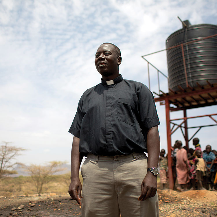 Father Fabian Hevi stands in front of elevated water tank in the Diocese of Lodwar, Kenya