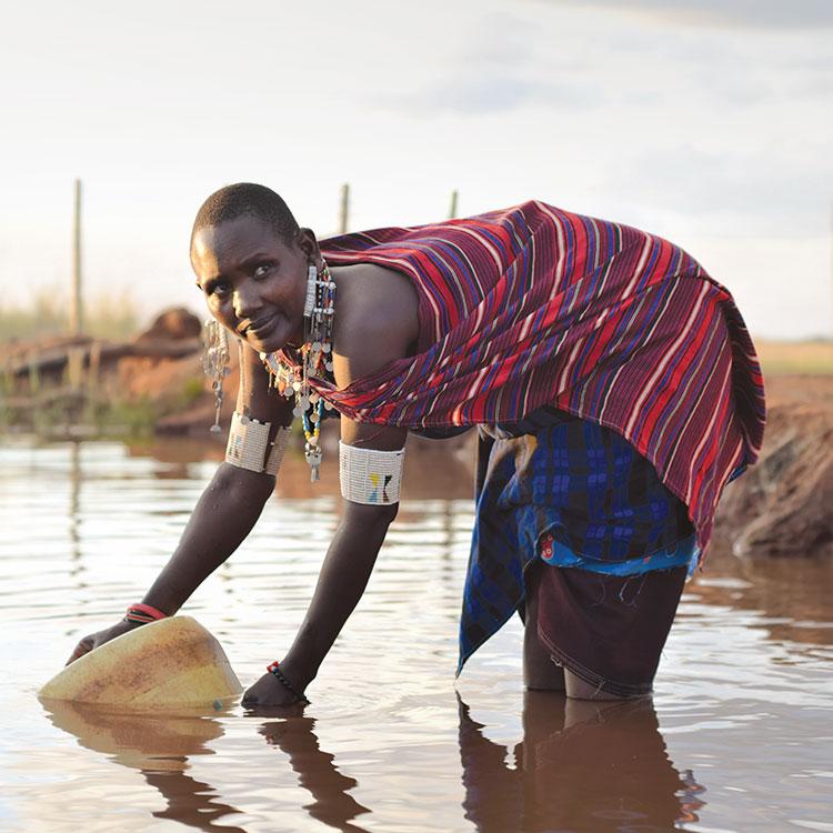 Maasai woman collects water from muddy lake near Orkung'u, Kenya
